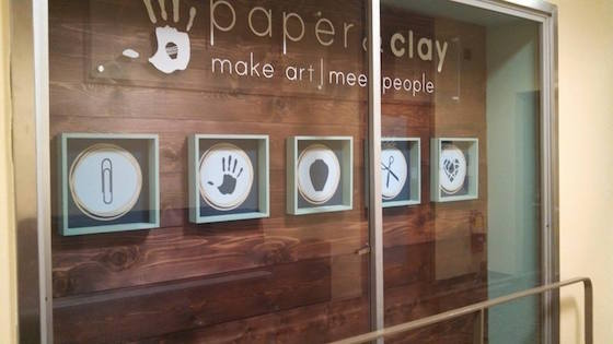 Display case with handprints outside of Paper & Clay.