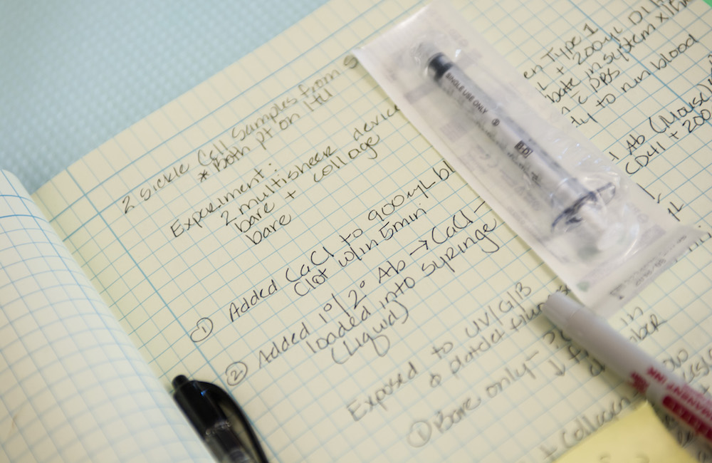 Lab notebook and syringe.