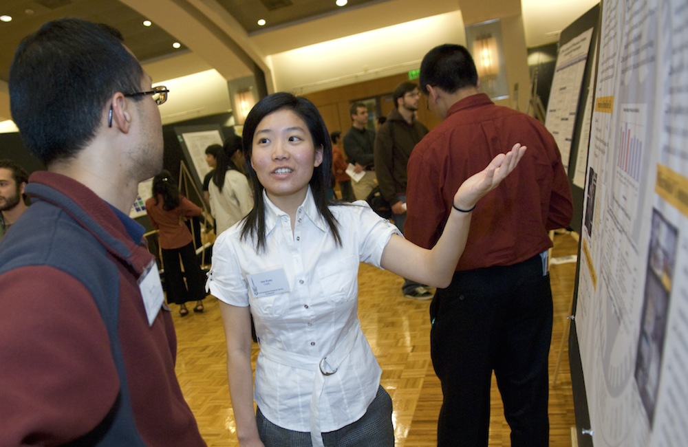 A student actively presenting her research poster to a fellow student.